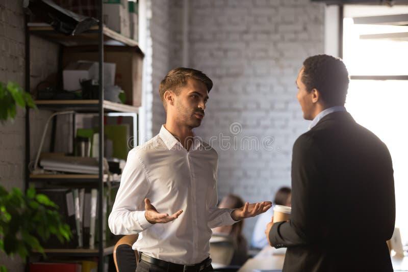 Employés masculins divers de société se tenant au bureau et à parler photo libre de droits