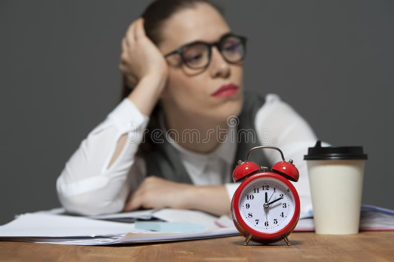 Employ? de bureau fatigu? ? la table avec les papiers et le r?veil rouge photographie stock