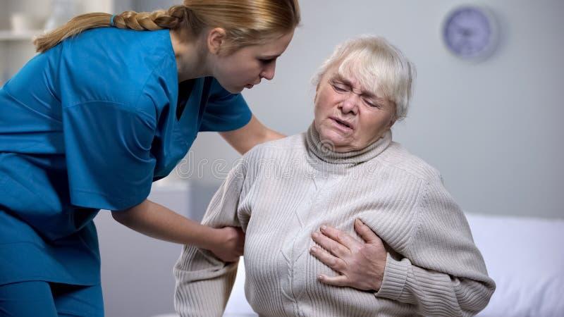 Employ? de maison de repos prenant le soin au sujet de la douleur se sentante de coeur de vieille dame, soins de sant? photographie stock libre de droits