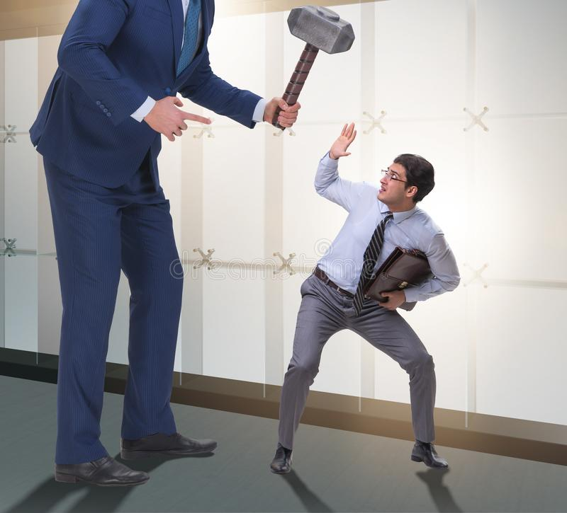 Employ? mena?ant de mauvais patron f?ch? avec le marteau photos stock