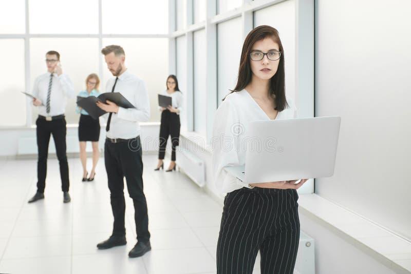 Employ?s de la position de soci?t? dans un lobby de bureau spacieux photos stock