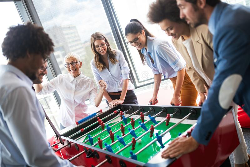 Employ?s jouant le jeu d'int?rieur du football de table dans le bureau pendant le temps de coupure photos stock