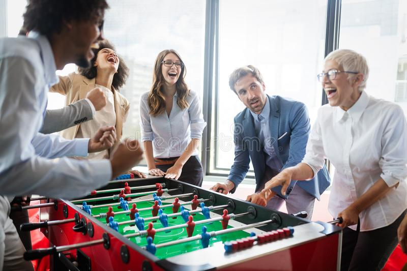 Employ?s jouant le jeu d'int?rieur du football de table dans le bureau pendant le temps de coupure photographie stock
