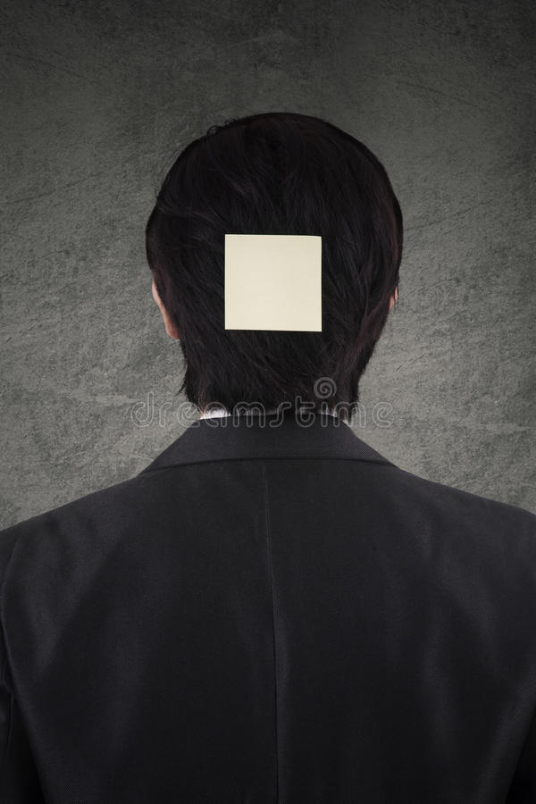 Employee attaching post it on head stock photography