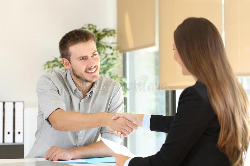 Employee and boss handshaking after a job interview. Happy employee and boss handshaking after a successful job interview at office royalty free stock photography