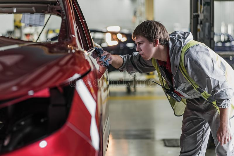 An employee of the car body painting shop checks the quality stock photo