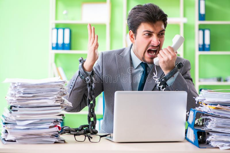 The employee chained to his desk due to workload. Employee chained to his desk due to workload stock image