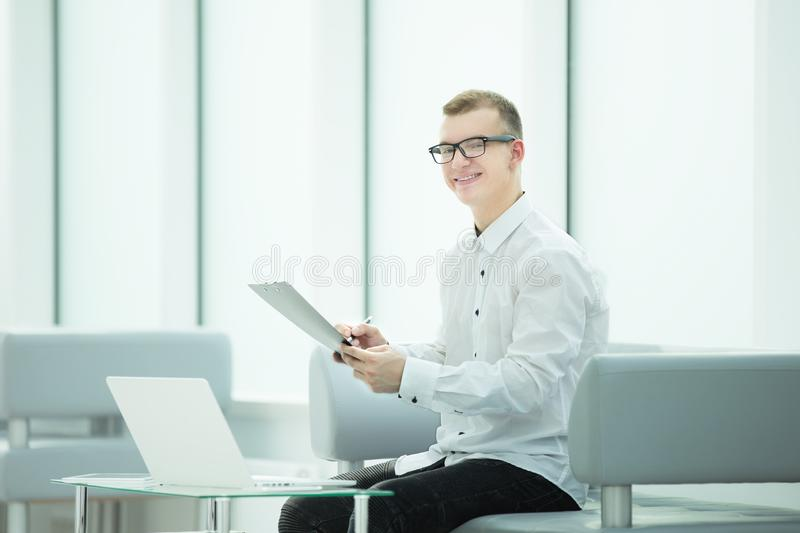 Employee of the company reads a business document sitting in the office lobby. Photo with copy spac stock photography