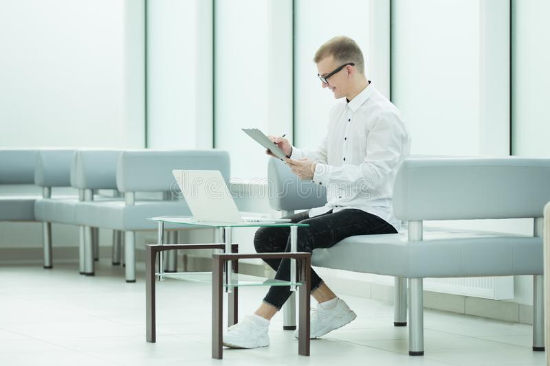 Employee of the company reads a business document sitting in the office lobby. Photo with copy spac royalty free stock images