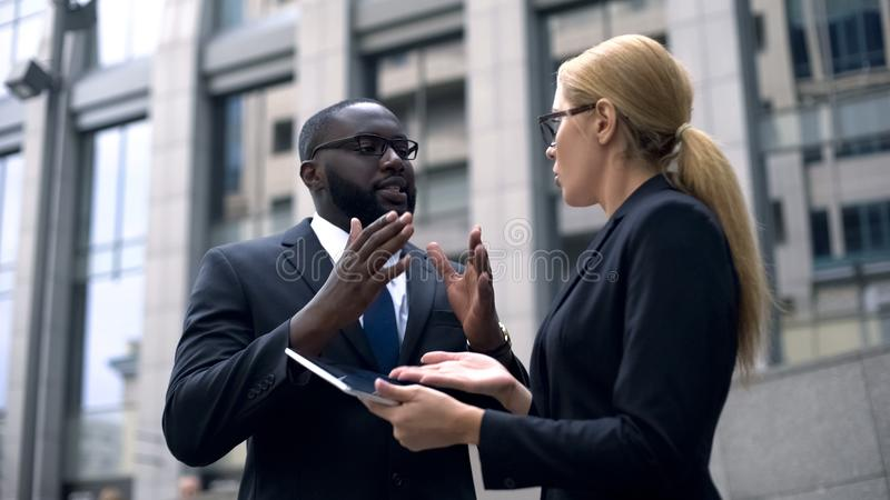 Employee convinces female boss of project profitability, shows income on tablet. Stock photo stock images