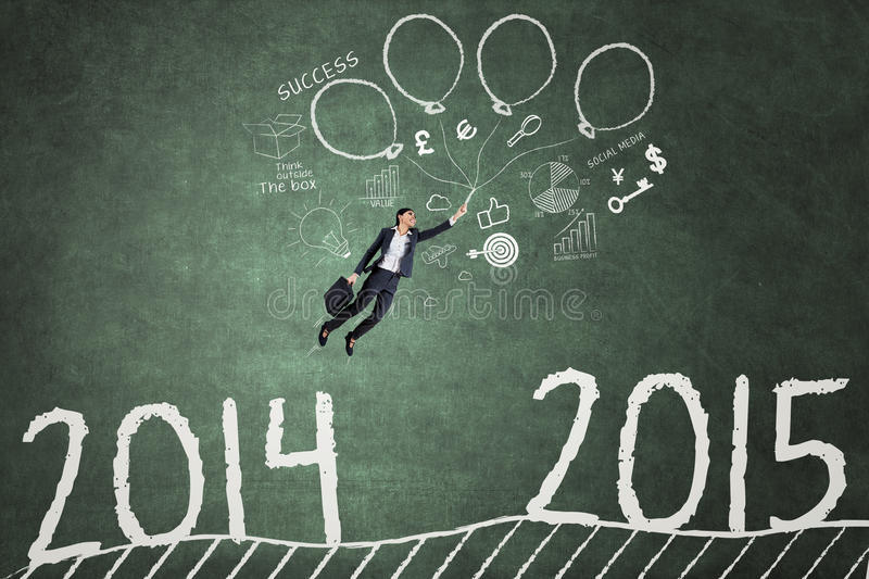 Employee flying over the number 2014 to 2015. Businesswoman using balloons to fly above number 2014 to 2015 and chase her success in future royalty free stock images