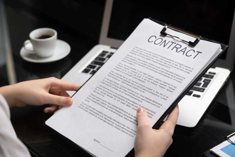 Employee gets acquainted with contract in stylish office royalty free stock photos