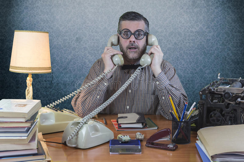 Employee with glasses talking on the phone in the office royalty free stock images