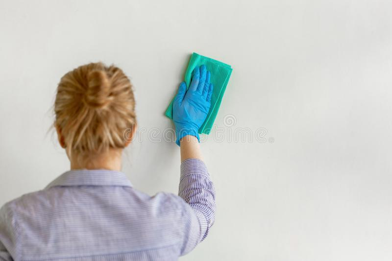 Employee hand in blue rubber protective glove wiping wall from dust with dry rag. Commercial cleaning company stock image