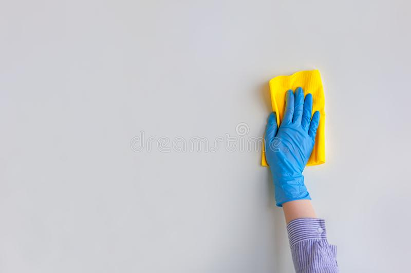 Employee hand in blue rubber protective glove wiping wall from dust with dry rag. General or regular cleanup stock image