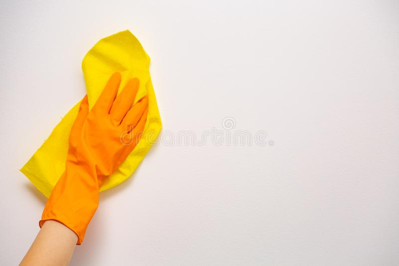 Employee hand in orange rubber protective glove wiping white wall from dust with yellow dry rag. General or regular cleanup. Commercial cleaning company. Copy stock images