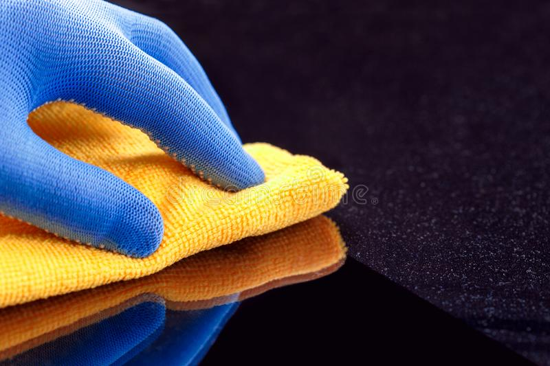 Employee hand in protective glove wiping dust layers on the furniture. With yellow dry rag stock photography