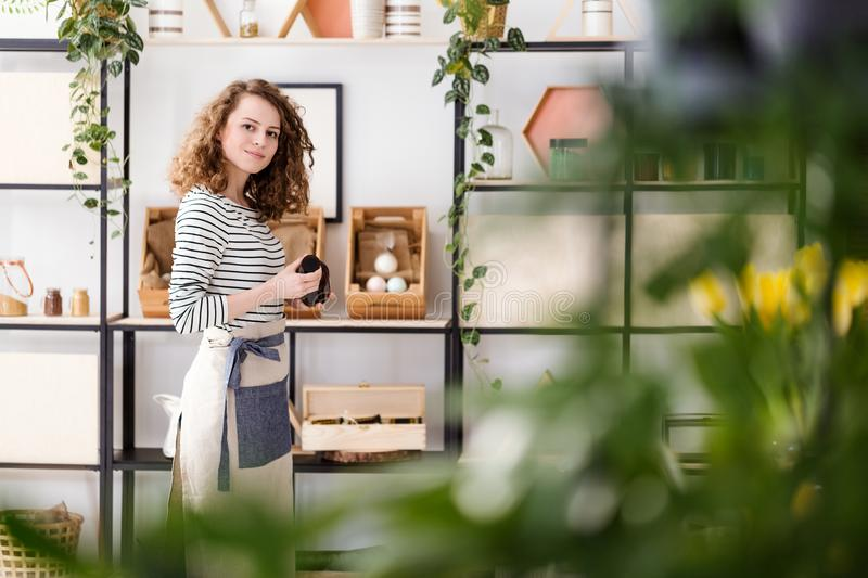 Employee holding organic skincare product. View through blurry leaves on a female employee in apron holding an organic skincare product in a shop with vegan stock image
