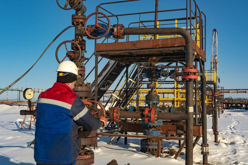 An employee of an oil company performs work in an oil field well. An employee of an oil company performs work on the well. It rotates the steering wheel on the royalty free stock photos