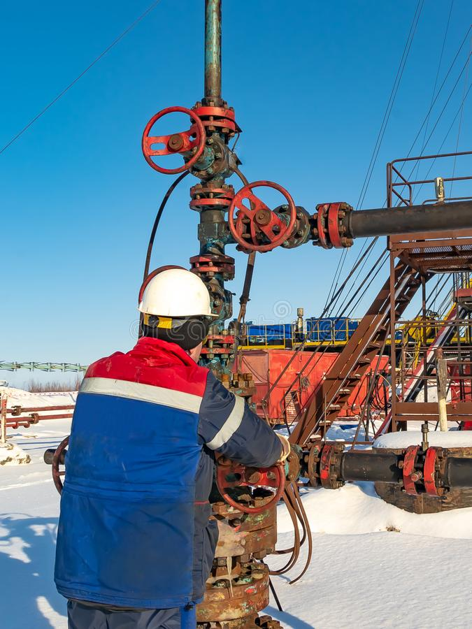 An employee of an oil company performs work in an oil field well. An employee of an oil company performs work on the well. It rotates the steering wheel on the royalty free stock photo