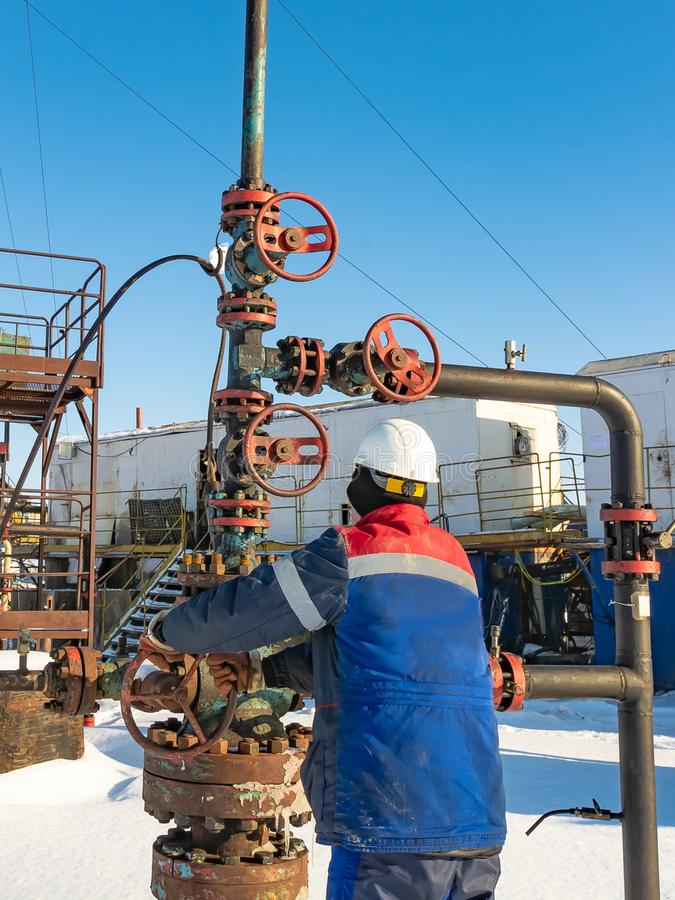 An employee of an oil company performs work in an oil field well. An employee of an oil company performs work on the well. It rotates the steering wheel on the stock images