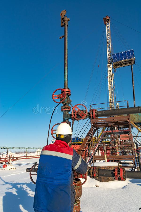 An employee of an oil company performs work in an oil field well. An employee of an oil company performs work on the well. It rotates the steering wheel on the stock image