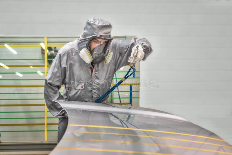 Employee of the paint shop of automobile factory conducts training on painting body parts royalty free stock photo