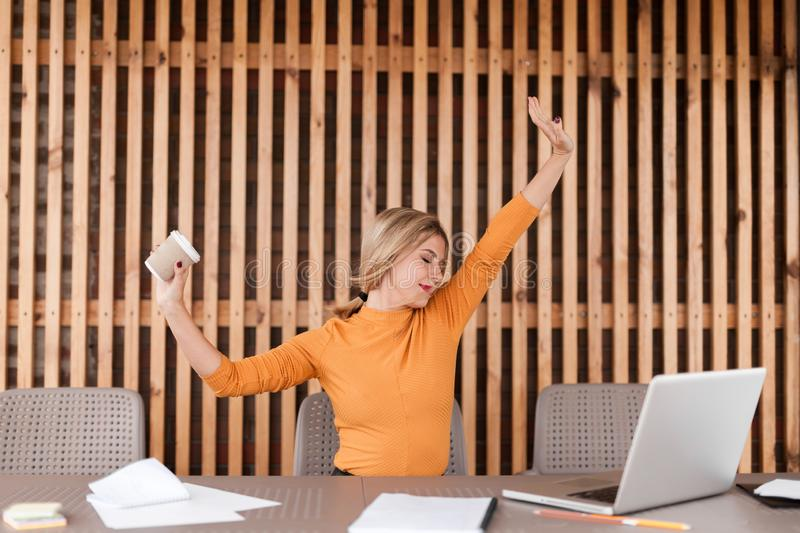 Employee pretty young woman relax in workplace. Stretching her arms stock photos