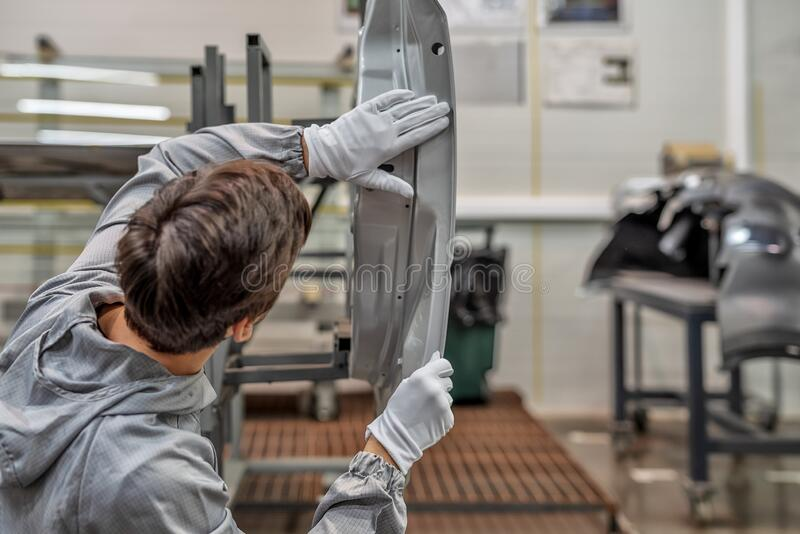 An employee of the quality Department of the car body paint shop checks the quality of applying the sealant stock image