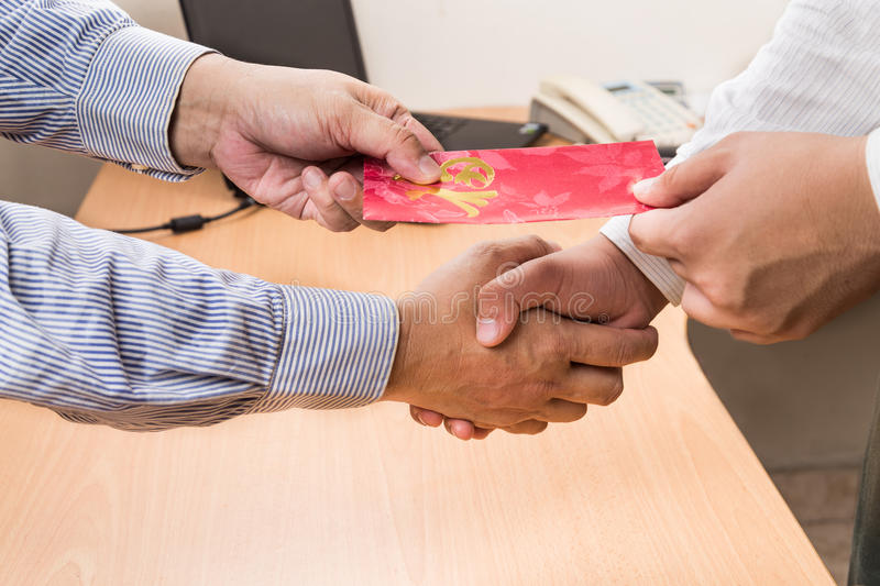Employee receiving red packet with Good Fortune wordings, from e. Employee receiving red packet with Good Fortune Chinese wordings, from employer upon returning stock image