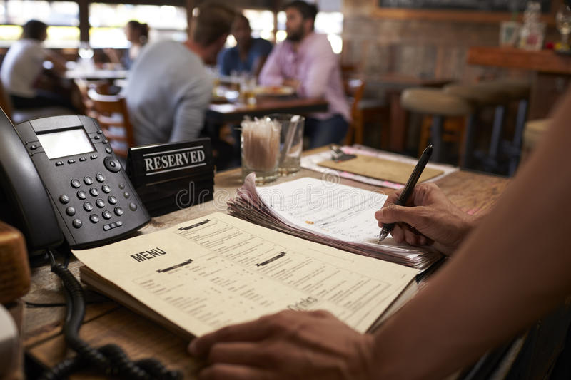 Employee at a restaurant writing down a table reservation stock photo