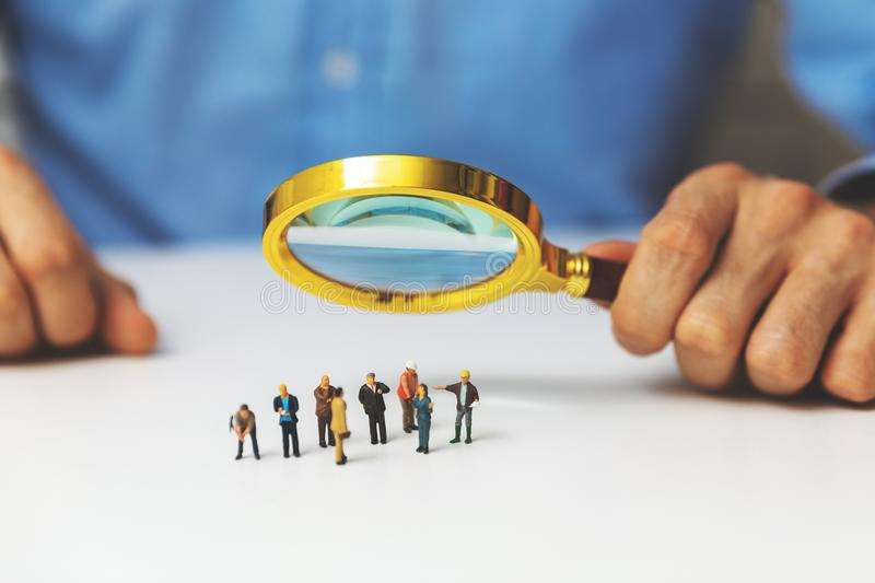 Employee search staff selection concept - recruitment manager with magnifying glass. In hand royalty free stock images