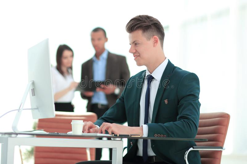 Employee sitting behind a Desk in the office . Photo with copy space stock image