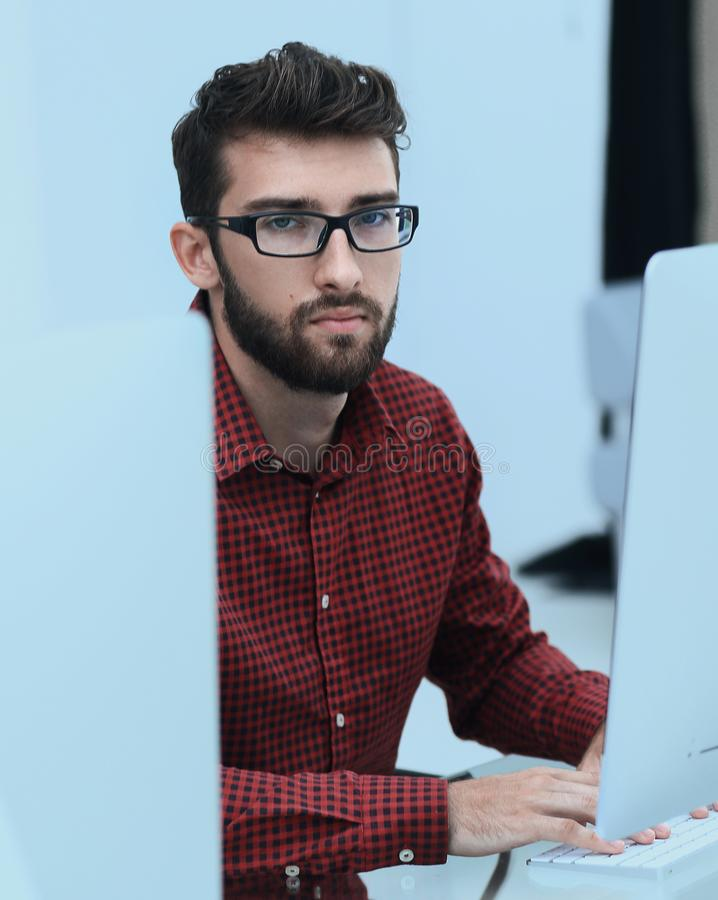 Employee sitting in front of a computer monitor. Photo with copy space royalty free stock photos