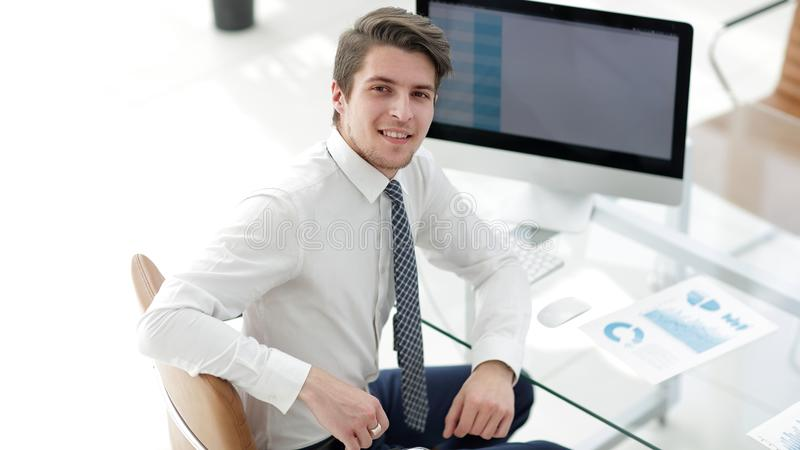 Employee sitting in front of a computer screen. Successful employee sitting in front of a computer screen.photo with copy space royalty free stock photo