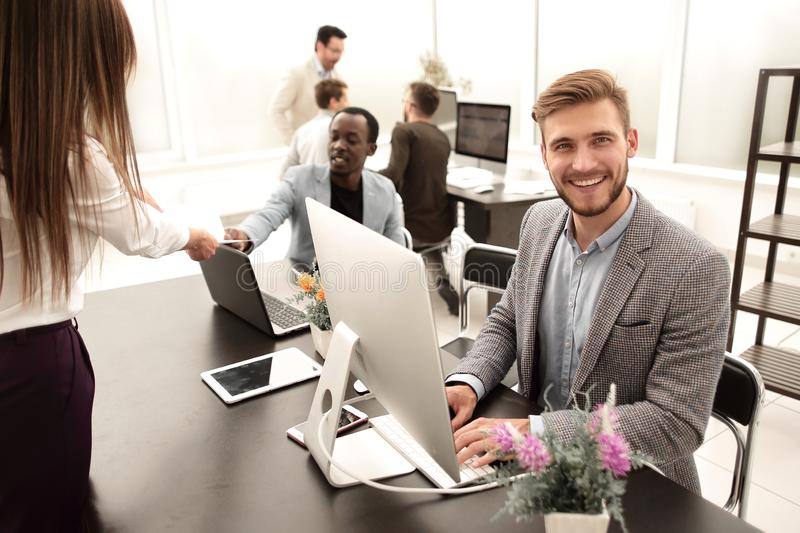 Employee sitting at his Desk in the office. Business people stock photo
