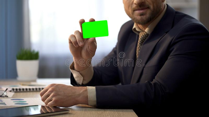 Employee sitting at office desk, showing card in green color, insurance plan stock photos