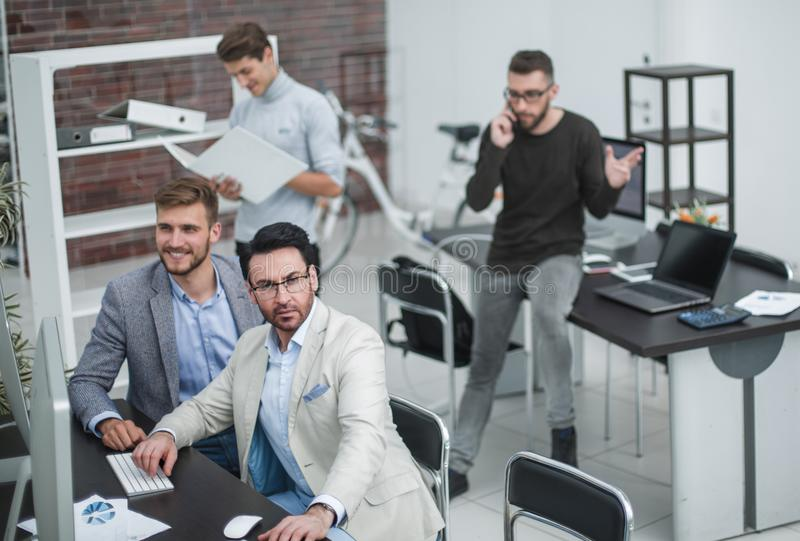 Employee talking on a mobile while sitting on office Desk. Photo with copy space royalty free stock photography