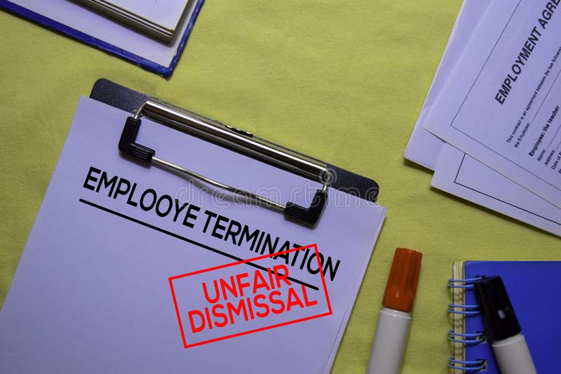 Employee Termination text on Document form and Stamp Unfair Dismissal isolated on office desk. stock photo