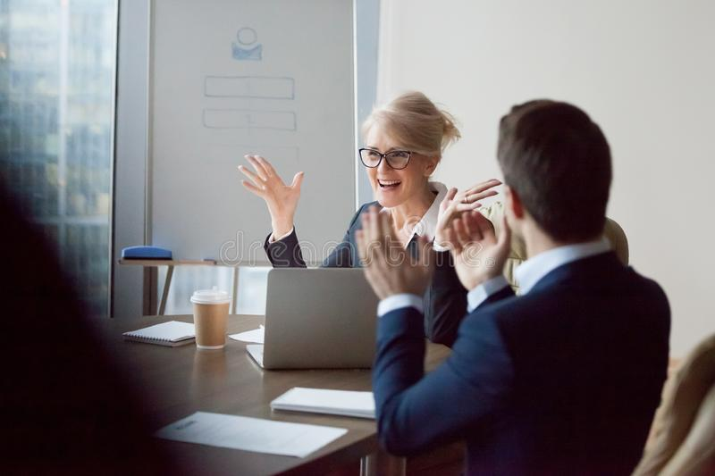 Employees applaud congratulating female boss with success. Colleagues congratulating middle aged female boss with high work achievement at meeting, employees royalty free stock photo