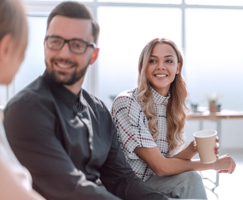 Employees of the company with coffee glasses sitting in the office lobby stock photo