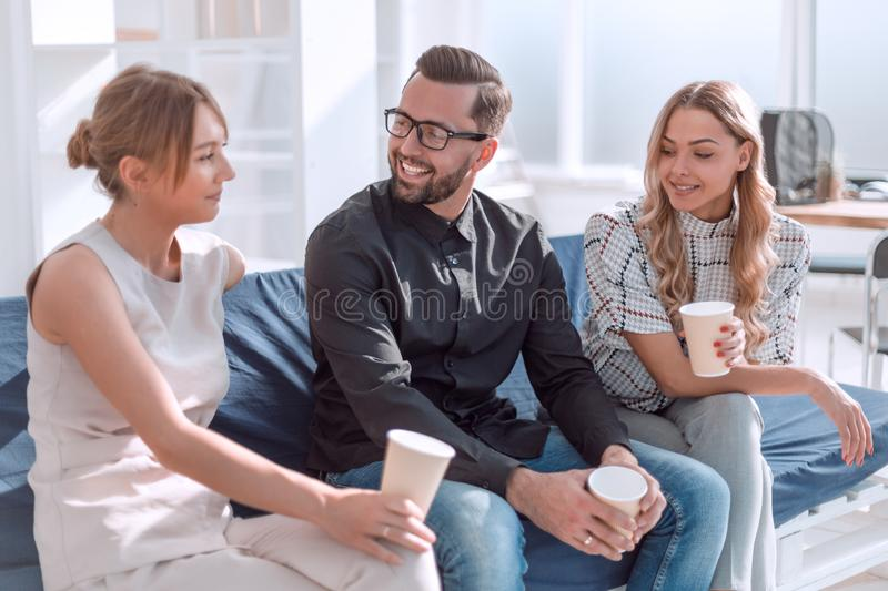 Employees of the company with coffee glasses sitting in the office lobby stock images