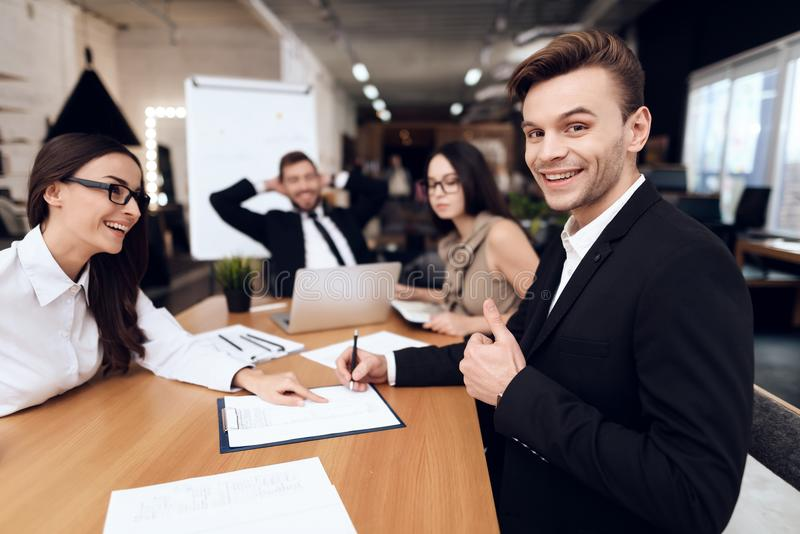 Employees of the company hold a meeting at the table. They are dressed in business suits. They talk about business stock photos