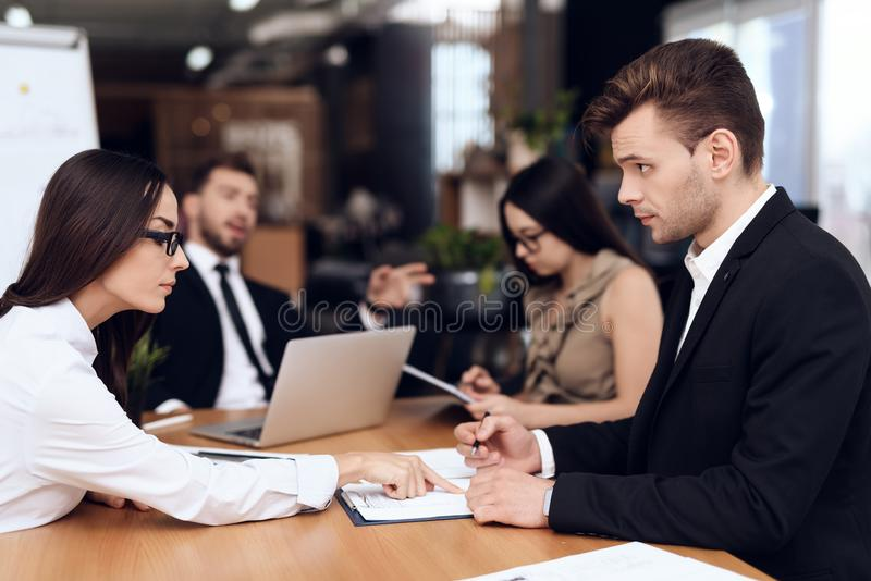 Employees of the company hold a meeting at the table. They are dressed in business suits. They talk about business royalty free stock image