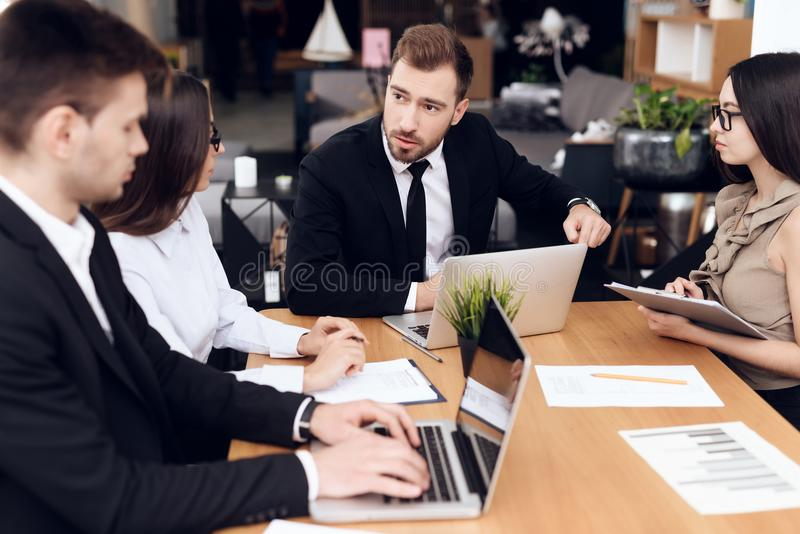 Employees of the company hold a meeting at the table. They are dressed in business suits. They talk about business royalty free stock photos