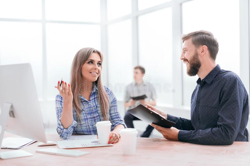 Employees discussing business documents in the office stock image