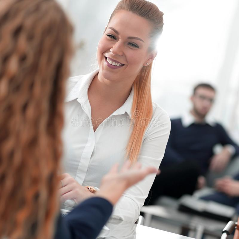 Employees discussing ideas sitting at his Desk stock photos