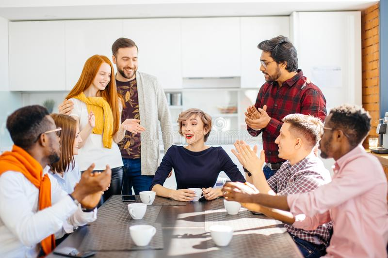 Employees enjoying spending time togeter while drinking coffee. In office kitchen royalty free stock images