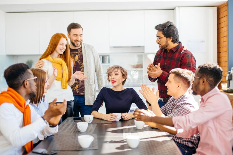 Employees enjoying spending time togeter while drinking coffee. In office kitchen stock photo
