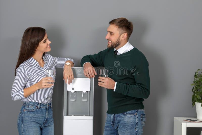 Employees having break near water cooler. In office royalty free stock photography